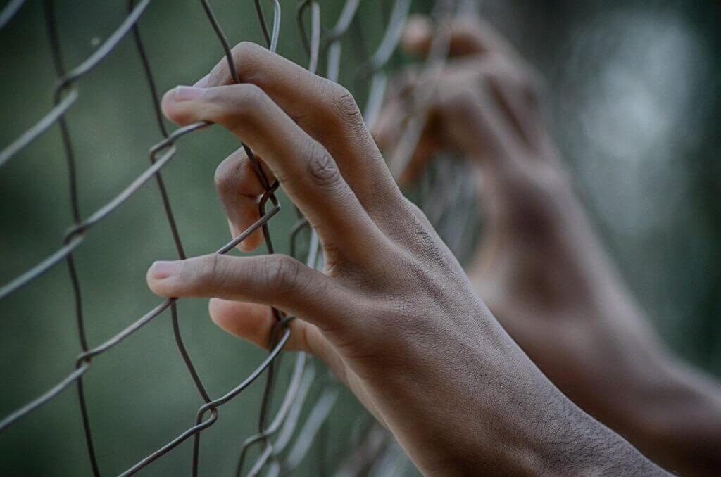manos que toman con fuerza un alambrado - esta nota habla sobre los desafíos que enfrenta Alejandro Mayorkas en la frontera méxico estados unidos
