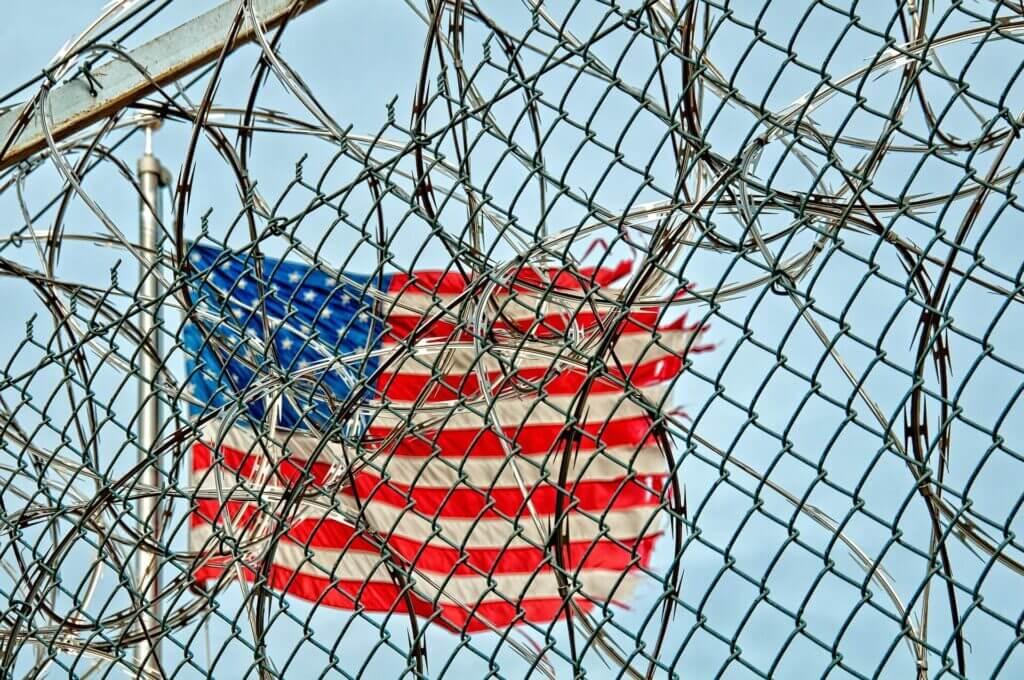Bandera de Estados Unidos detrás de un alambrado - Este artículo habla acerca del creciente número de niños no acompañados en la frontera y la colaboración de FEMA.